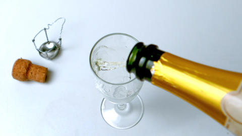 Champagne being poured into flute on white surface Footage