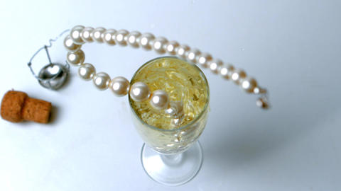 String of pearls dropping in glass of champagne Footage