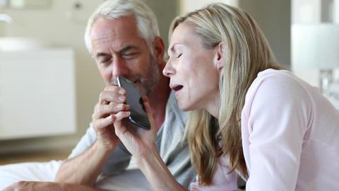 Man jokingly taking phone off partner talking Footage