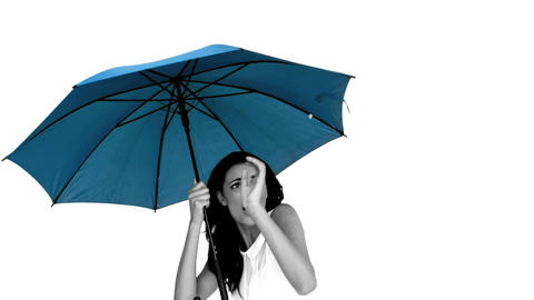 Woman under blue umbrella cowering with fear Footage