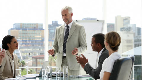 Businessman presenting to his team who applaud him Footage
