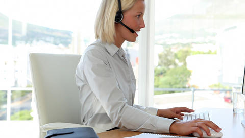 Blonde haired businesswoman working with a headset Footage