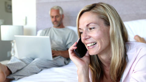 Woman laughing while she is on the phone next to his husband on his laptop Footage
