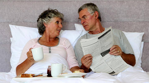 Husband reading the newspaper to his wife during breakfast Footage