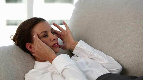 Businesswoman lying on sofa touching her temples Footage