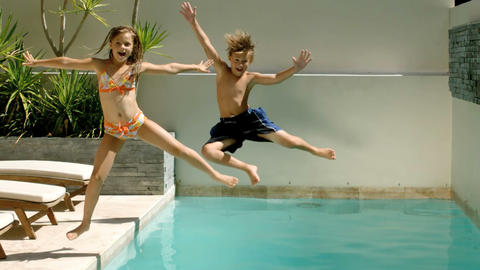 Happy siblings diving into the swimming pool Footage