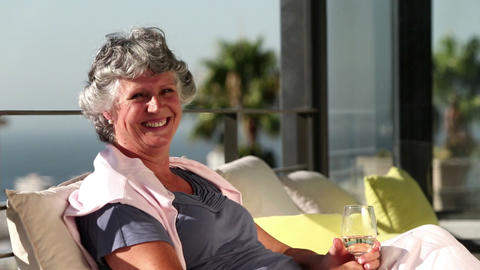 Mature woman smiling at camera on balcony Footage