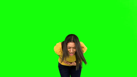 Woman suffering from belly pain on green screen Live Action