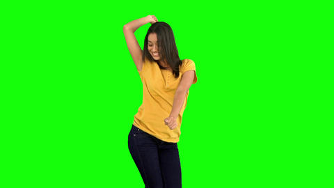 Woman dancing with arms raised on green screen Footage