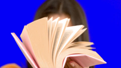 Woman flipping through a pink book on blue screen Footage