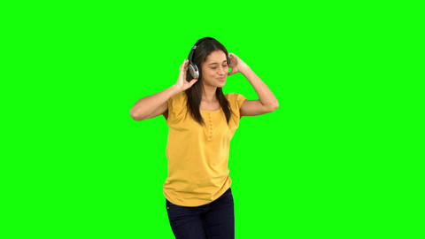 Woman dancing with headphones on green screen Footage
