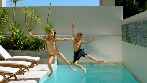Brother and sister diving into the swimming pool Footage