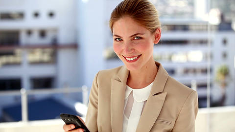 Portrait of smiling businesswoman text messaging Live Action