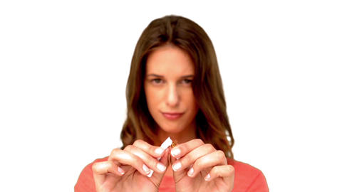 Brunette woman breaking a cigarette on white background Footage