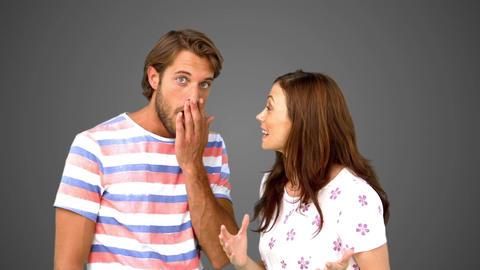 Woman telling her friend a massive secret on grey background Footage