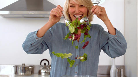 Smiling woman tossing her salad Footage