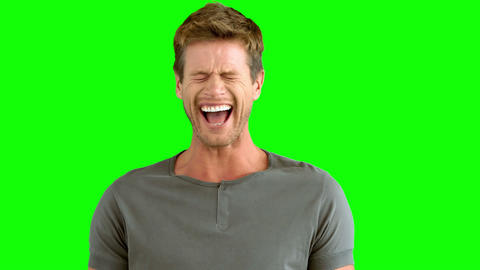 Handsome man laughing on green screen Footage