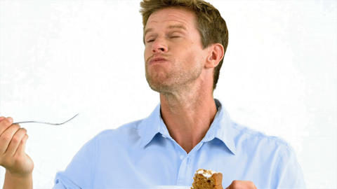 Man savouring a delicious cake on white background Live Action