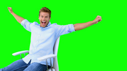 Man sitting on swivel chair with raised arms to show his success on green screen Live Action