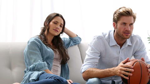 Woman annoyed by her partner watching basketball game Live Action