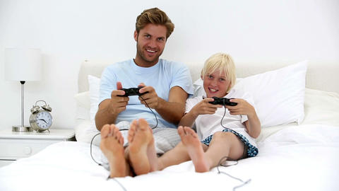 Father and son playing video games together Footage