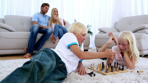 Parents watching their children play chess togethe Footage