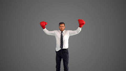 Businessman in boxing gloves leaping and punching  Footage
