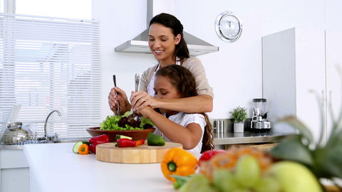 Mother and daughter tossing salad together Footage