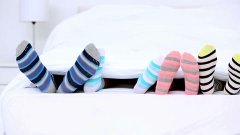Familys feet in stripey socks kicking under the covers Live Action