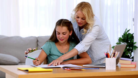 Mother helping her daughter with homework and smil Footage