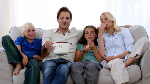 Family watching tv and eating popcorn Footage