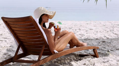 Happy woman drinking a cocktail on the beach Footage