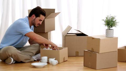 Man unpacking tableware Footage