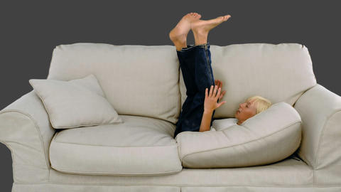Young boy jumping on the sofa on grey background Footage