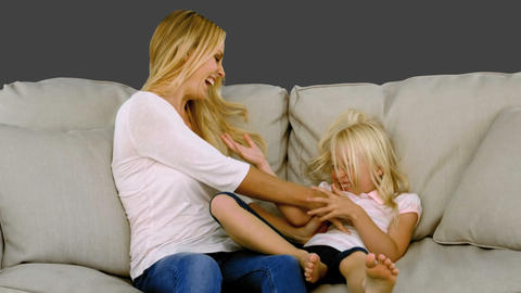 Mother tickling her daughter on sofa Footage