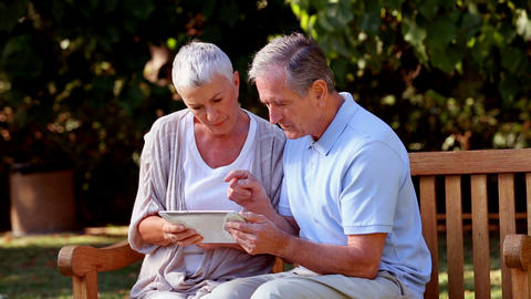 Mature couple using tablet computer on a bench Footage
