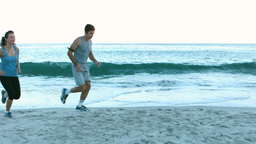 Sporty people running on the beach Footage