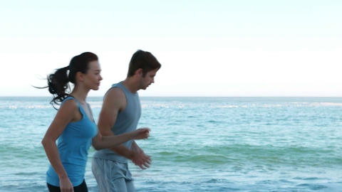 Couple running side by side on the beach Live Action