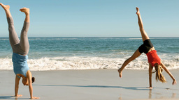 Two women doing cartwheels on the beach Footage