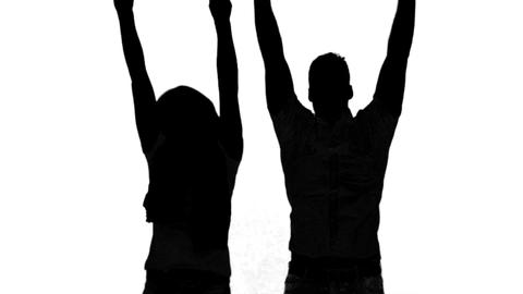 Silhouette of couple jumping and raising arms on white background Live Action
