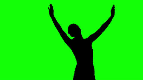 Silhouette of woman raising arms on green screen Live Action