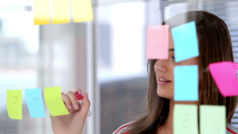Woman writing on sticky note Live Action