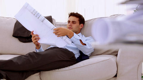 Businessman lying on couch and looking at a document Footage