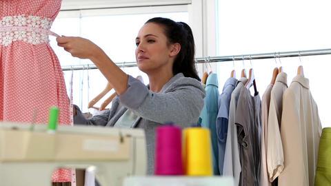 Pretty fashion designer measuring a dress Footage