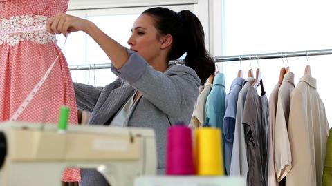 Pretty fashion designer measuring the belt of a dress Footage