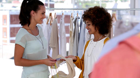 Woman with shopping bags talking with a friend Footage
