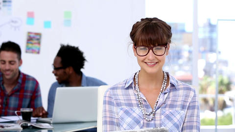 Cheerful designer posing while her colleagues are working together Footage