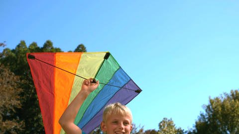 Young boy running while holding a kite Footage