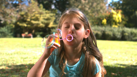 Smiling young girl blowing into a bubble wand Footage