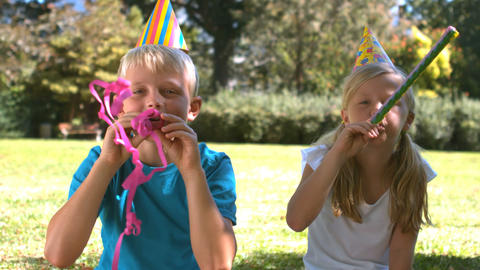 Siblings with party hat having fun with party horn Live Action